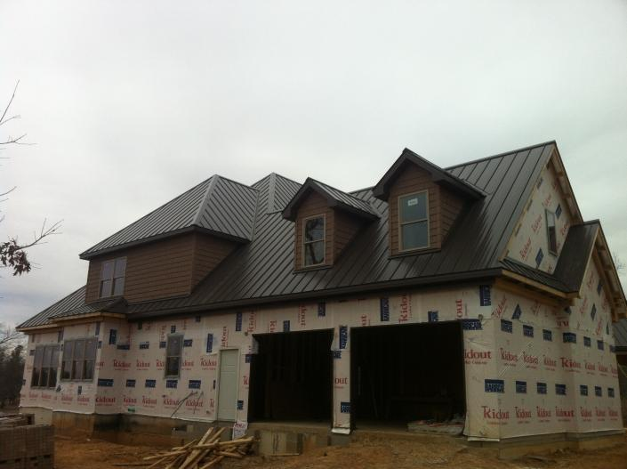 [Image: Installing metal roofs on a new home. ]